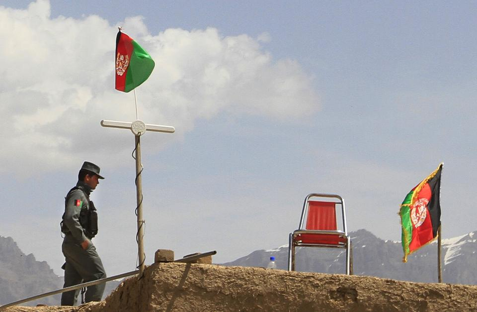 An Afghan policeman stands guard on the roof of a house in the outskirts of Kabul, Saturday, April 6, 2013. NATO says a blast in Afghanistan has killed four coalition service members and two civilians working with the alliance. The blast from a roadside bomb occurred Saturday in southern Afghanistan.(AP Photo/Jawad Jalali)
