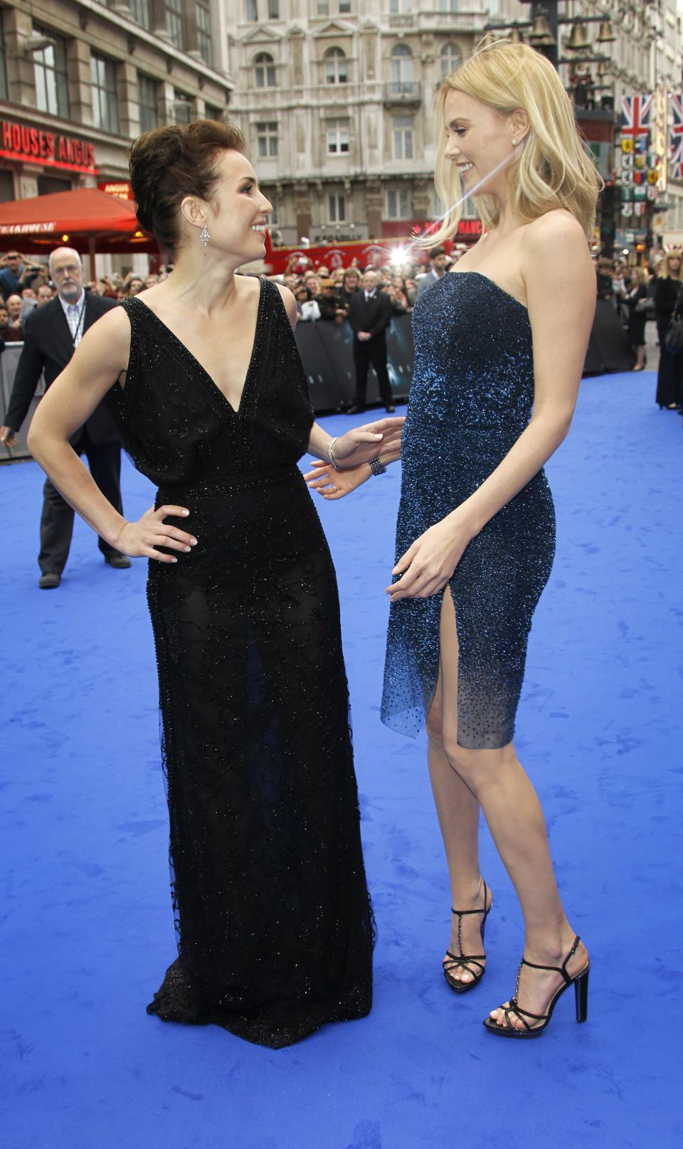 Actresses Noomi Rapace, left, and Charlize Theron greet each other on the blue carpet as they arrive at a central London cinema for the World Premiere of Prometheus, Thursday, May 31, 2012. (AP Photo/Joel Ryan)