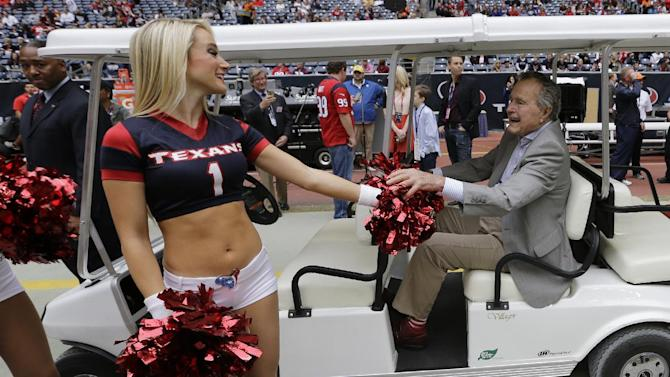 Former United States President George H. W. Bush, right, greets a Houston Texans cheerleader before an NFL football game against the New England Patriots, Sunday, Dec. 1, 2013, in Houston