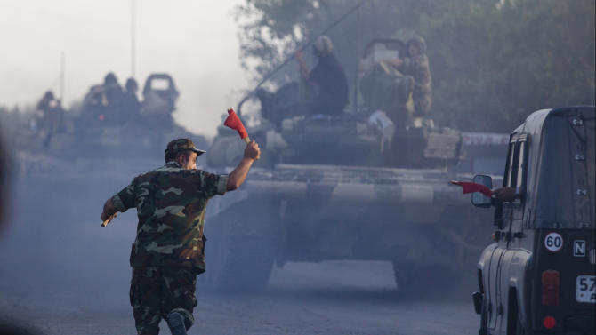 In this Saturday, Aug. 2, 2014, photo a convoy of Azerbaijan's Army tanks moves in the direction of Agdam, Azerbaijan. Recent days have seen a sharp escalation in fighting between Azerbaijan and Armenia around a tense line of control around Nagorno-Karabakh. (AP Photo/Abbas Atilay)