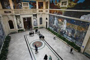 People at a mural by artist Diego Rivera at the Art Institute of Detroit in Detroit