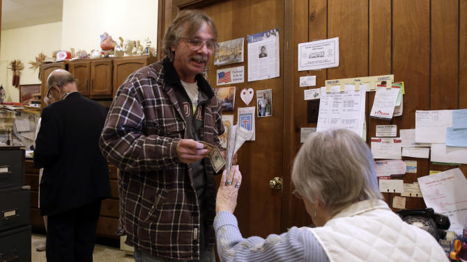 In this Tuesday, Oct. 30, 2012 photo, receptionist Edith Moore, right, holds up her hand to refuse $5 from patient Joe Logsdon, center, for his office visit as Dr. Russell Dohner, left, walks to his next waiting patient in Rushville, Ill. Dohner decided there would be no charge for Logsdon's visit since Logsdon only came in to have the doctor look at cholesterol test results. (AP Photo/Jeff Roberson)