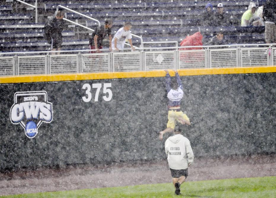 A fan tries to escape from security up the outfield wall on Wednesday June 20, 2012, while waiting for the rain to pass at the NCAA College World Series elimination game between Kent State and South Carolina in Omaha, Neb. (AP Photo/Dave Weaver)