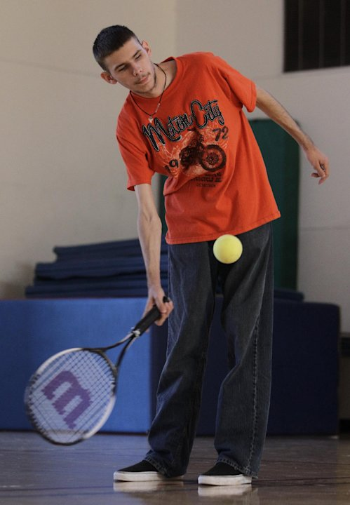 In this photo taken Oct. 16, 2012, Austin Benavidez, who is blind, returns a volley using an oversized ball filled with ball bearings at the California School for the Blind in Fremont, Calif. Students