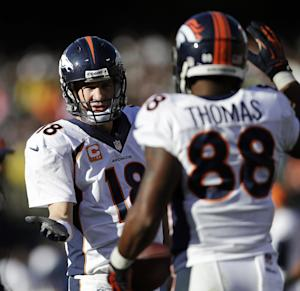 Denver Broncos quarterback Peyton Manning (18) celebrates with wide receiver Demaryius Thomas (88) after they connected for a 5-yard touchdown against the Oakland Raiders during the second quarter of an NFL football game, Sunday, Dec. 29, 2013, in Oakland, Calif. With that completion, Manning set the all-time single season passing yardage record. (AP Photo/Marcio Jose Sanchez)