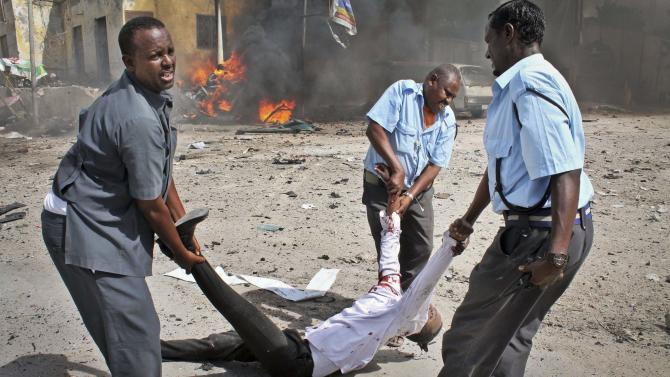 Somali security force members carry away a severely wounded man following a suicide car bomb blast in the capital Mogadishu, Somalia, Sunday, May 5, 2013. A Somali police official at the scene said four civilians and a soldier were killed after the bomber attempted to ram a car laden with explosives into a military convoy. (AP Photo/Farah Abdi Warsameh)