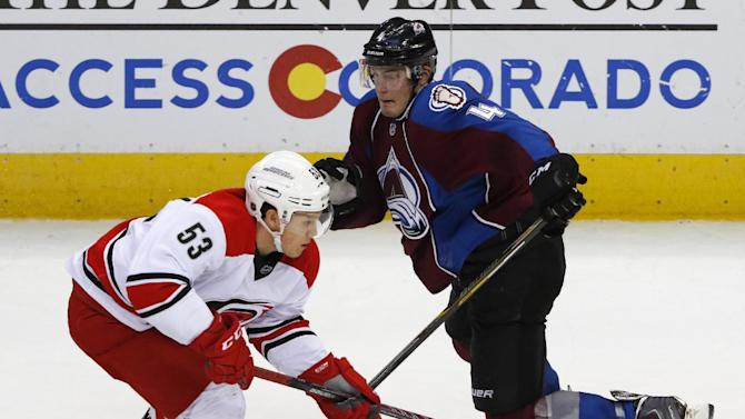 Carolina Hurricanes left wing Jeff Skinner (53) moves the puck past Colorado Avalanche defenseman Tyson Barrie (4) during the third period of an NHL hockey game Saturday, Nov. 22, 2014, in Denver. Colorado won 4-3. (AP Photo/Jack Dempsey)