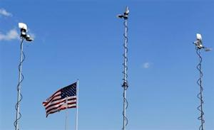 Transmission masts from television trucks are seen around an U.S. flag above Sanford City Hall following a news conference in Sanford, Florida