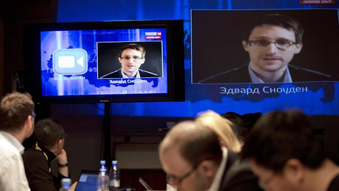 Edward Snowden, displayed on television screens, asks a question to Russian President Vladimir Putin during a nationally televised question-and-answer session, in Moscow, Thursday, April 17, 2014. Speaking in a televised call-in show with the nation, Putin harshly criticized the West for trying to pull Ukraine into its orbit and said that people in eastern Ukraine have risen against the authorities in Kiev, who ignored their rights and legitimate demands. Putin also took a video question from National Security Agency leaker Edward Snowden, whom Russia granted asylum last year. Asked by Snowden about Russia's surveillance programs, Putin said that Russian special services also tap on communications in their fight against terrorism, but don't do it on such a massive scale as the U.S. (AP Photo/Pavel Golovkin)