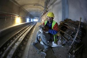 A worker holds a cat in the Marmaray Tunnel under the …