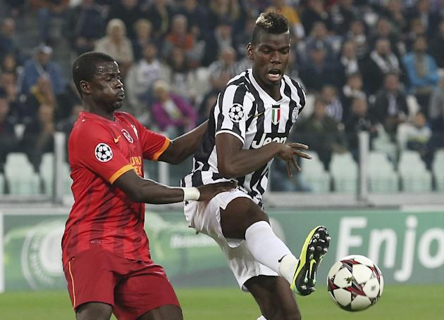Juventus midfielder Paul Pogba, right, of France, challenges for the ball with Galatasaray defender Emmanuel Eboue, of Ivory Coast, during a Champions League, Group B, soccer match  at the Juventus st