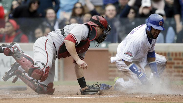 Arizona Diamondbacks catcher Miguel Montero, left, applies a late tag as Chicago Cubs' Emilio Bonifacio scores on a ball hit by Anthony Rizzo during the first inning of a baseball game in Chicago, Thursday, April 24, 2014. (AP Photo/Nam Y. Huh)