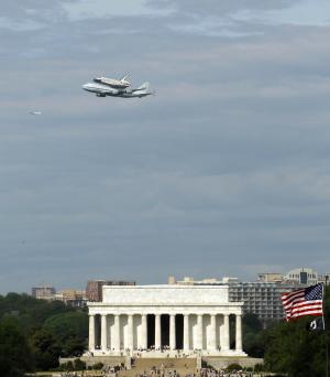 The Space Shuttle Discovery, mounted on the Shuttle Carrier Aircraft, flies over the Lincoln Memorial in Washington, Tuesday, April 17, 2012. Discovery is en route from Kennedy Space Center to the Smithsonian National Air and Space Museum Udvar/Hazy Center at Dulles International Airport. (AP Photo/Ann Heisenfelt)