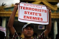An ethnic Rakhine demonstrator holds a sign as hundreds protest at Yangon&#39;s Shwedagon pagoda after unrest flared in the western Myanmar state. Security forces have tried to restore order to a Myanmar state placed under emergency rule after a wave of deadly religious violence, as the United Nations evacuated foreign workers