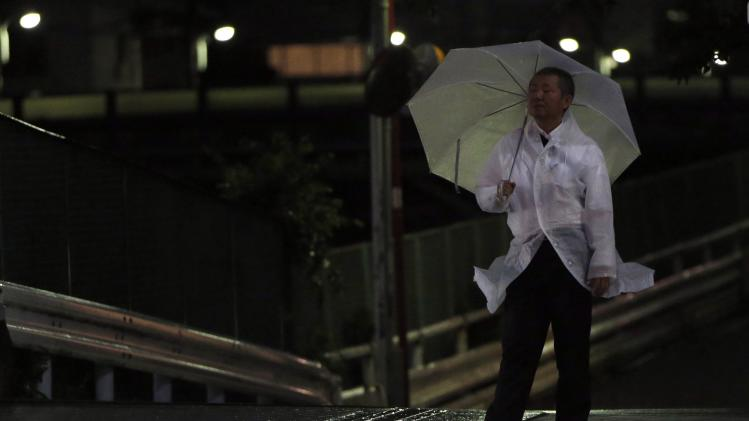 A man wearing a raincoat waits for a traffic light to turn green in Tokyo