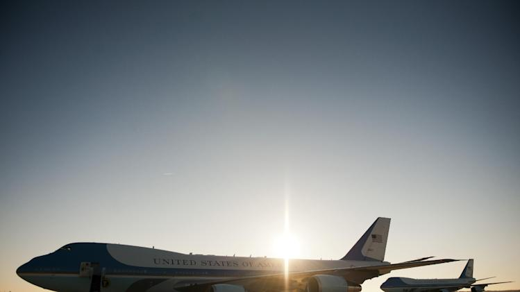 Air Force One, left, and the back-up aircraft, await the arrival of President Barack Obama at Andrews Air Force Base, Md. at sunrise, Saturday, Nov. 17, 2012, for his trip to Southeast Asia. (AP Photo/Cliff Owen)