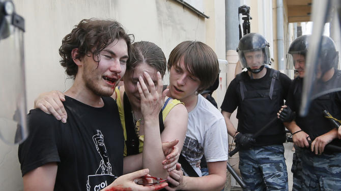 FILE - In this Saturday, June 29, 2013 file photo riot police (OMON) guard gay rights activists who have been beaten by anti-gay protesters during an authorized gay rights rally in St.Petersburg, Russia. Police detained several gay activists, who were outnumbered by the protesters. Dozens of gay activists had to be protected by police as they gathered for the parade, which proceeded with official approval despite recently passed legislation targeting gays. (AP Photo/Dmitry Lovetsky, file)