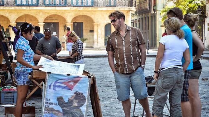 Tourists look at posters for sale in Havana, on December 18, 2014