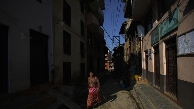Light illuminates a woman as she walks along alley at Khokana