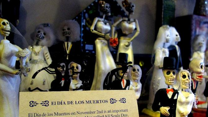 """In this May 8, 2013 photo, artwork is shown at Masks y Mas, an Albuquerque shop that sells 'Day of the Dead' art year round. Disney announced Tuesday that it was a withdrawing a """"Dia de los Muertos"""" trademark request it made to the U.S. Patent and Trademark Office amid uproar on social media from Latino activists, writer and artists. Disney had sought to secure naming right for an upcoming animated movie inspired by the holiday. Critics said the move to trademark a cultural holiday was insensitive.  (AP Photo/Russell Contreras)"""
