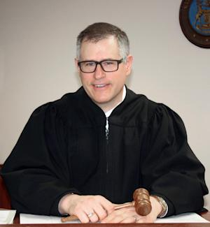 Judge Raymond Voet poses in his courtroom in Ionia, Mich., Monday, April 15, 2013. Voet, whose smartphone disrupted a hearing in his own courtroom, has held himself in contempt and paid $25 for the infraction. On Friday afternoon, during a prosecutor's closing argument as part of a jury trial, Voet's new smartphone began to emit sounds requesting phone voice commands. Voet said he thinks he bumped the phone, and the embarrassment likely left his face red. (AP Photo/Ionia Sentinel-Standard, Karen Bota)