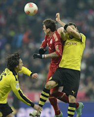 Dortmund&#39;s Mats Hummels (L) and Neven Subotic fight for the ball with Bayern Munich&#39;s Mario Mandzukic during their German first division Bundesliga match, in Munich, southern Germany, on December 1. Dortmund play Wolfsburg next, at home, on Saturday