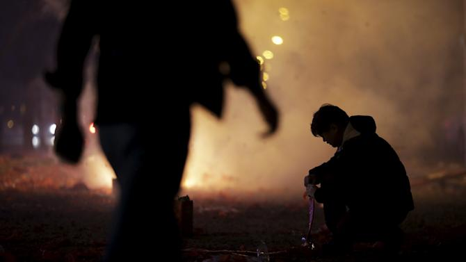 A man adds more firecrackers during celebrations for the start of the Chinese Lunar New Year of Monkey in Beijing