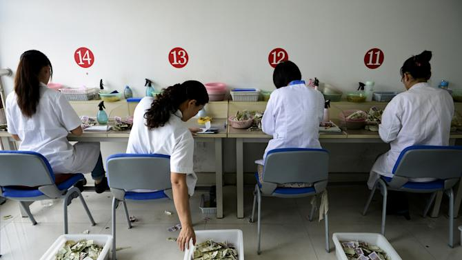 In this photo Sunday, Oct. 7, 2012, photo, workers count the small currency notes from bus fares at the accounting center of a bus company in Rizhao city in east China's Shandong province. A strong warning from the World Bank that growth in Asia may slow further dragged the price of oil Monday, Oct. 8, 2012, to its lowest close in two months.  (AP Photo) CHINA OUT