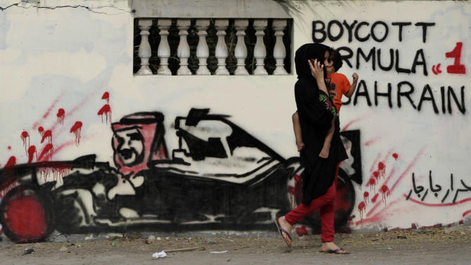 "A Bahraini carrying a child passes a wall Thursday, April 5, 2012, in Barbar, Bahrain, west of the capital of Manama, that is painted with graffiti depicting Bahrain's King Hamad bin Isa Al Khalifa in a race car, calling for a boycott of this year's Formula One Bahrain grand prix, scheduled for April 22. The Arabic is a signature reading ""free men of Barbar."" A year after an anti-government uprising forced Bahrain's rulers to cancel the kingdom's coveted Formula One race, the grand prix is again smack in the middle of a power struggle. (AP Photo/Hasan Jamali)"