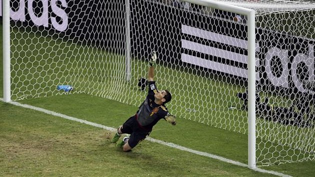 Spain's goalkeeper Iker Casillas dives as the penalty shot by Italy's Leonardo Bonucci (not pictured) goes over the bar during the penalty shootout of their Confederations Cup semi-final soccer match at the Estadio Castelao in Fortaleza June 27, 2013. REU