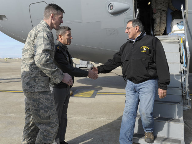 Defense Secretary Leon Panetta, right, walks off of his plane and  shakes hands with 10th Tanker Base Commander Brig. Gen Serdar Gulbas, center, Col. Christopher E. Craige, at left, Commander of the 3