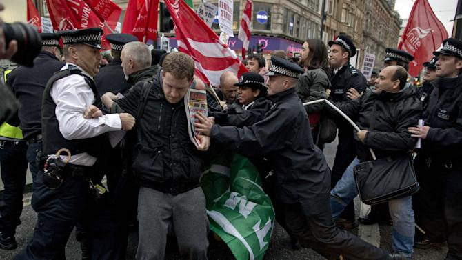 Police officers try to push protesters back onto the pavement after they blocked traffic on Oxford Street, London, whilst taking part in a picket and demonstration they said was over dismissals of 28 workers employed by contractors on the Crossrail transport project, for being trade union members, Wednesday, Nov. 14, 2012. The protest was held to coincide with planned European strikes on Wednesday in Spain, Italy, Greece, Portugal, France and Belgium against austerity measures and economic reforms. Crossrail, due to start running services in 2018, is a new train line that will include twin-bore 21 km tunnels under central London and link 37 stations including transport hubs such as Heathrow airport with business districts including the City and Canary Wharf. (AP Photo/Matt Dunham)