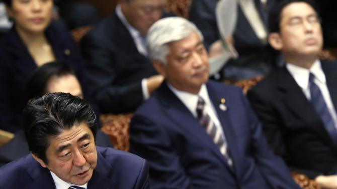 Japan's PM Abe speaks next to Defence Minister Nakatani and Foreign Minister Kishida during an upper house committee session at the parliament in Tokyo