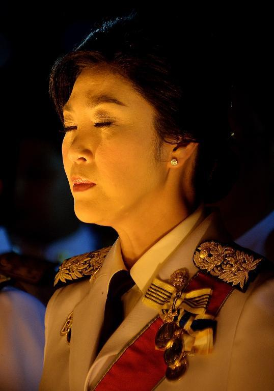 Thai Prime Minister Yingluck Shinawatra closes her eyes while in front of a portrait of King Bhumibol Adulyadej to celebrate his 86th birthday, on December 5, 2013