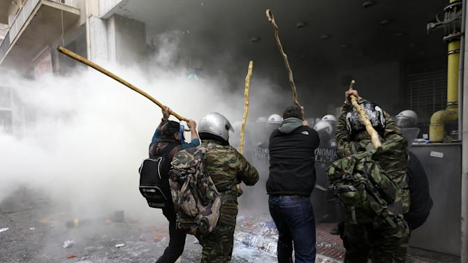 Farmers clash with riot police during a protest outside Agriculture ministry in Athens, Friday, Feb. 12, 2016. Farmers from across Greece have begun gathering in Athens for a two-day protest against the government and its plans to impose new tax hikes and pension charges. Bailout lenders are demanding that Greece scrap tax breaks for farmers and impose pension reforms that will lead to higher monthly contributions from the self employed and salaried employees. (AP Photo/Thanassis Stavrakis)