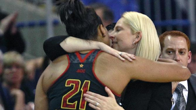 Maryland head coach Brenda Frese, right, embraces forward Tianna Hawkins during the closing minutes of a women's NCAA college regional semifinal basketball game against Connecticut in Bridgeport, Conn., Saturday, March 30, 2013. Connecticut won 76-50. (AP Photo/Charles Krupa)
