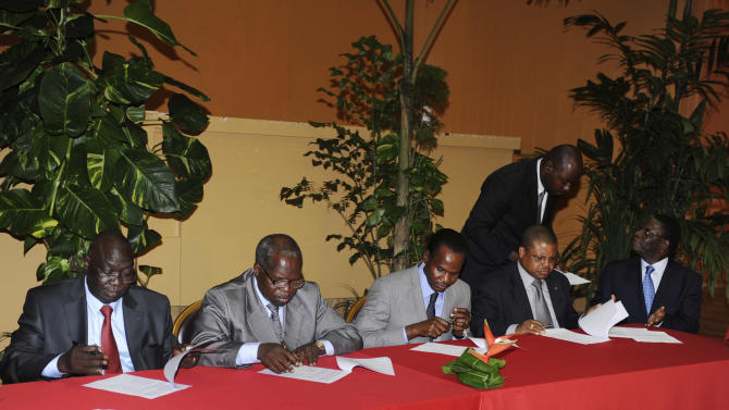Central African Republic peace talk participants, including Seleka rebel alliance leader Michel Djotodia, left, and Jean Willybiro Sako, second left, head of the Central African Republic's government delegation, sign a peace agreement, in Libreville, Gabon, Friday, Jan. 11, 2013. Officials say that the rebel group controlling much of the northern half of the Central African Republic have agreed to enter into a coalition with the government. The deal will allow President Francois Bozize to stay in office until his current term expires in 2016. (AP Photo/Joel Bouopda Tatou)