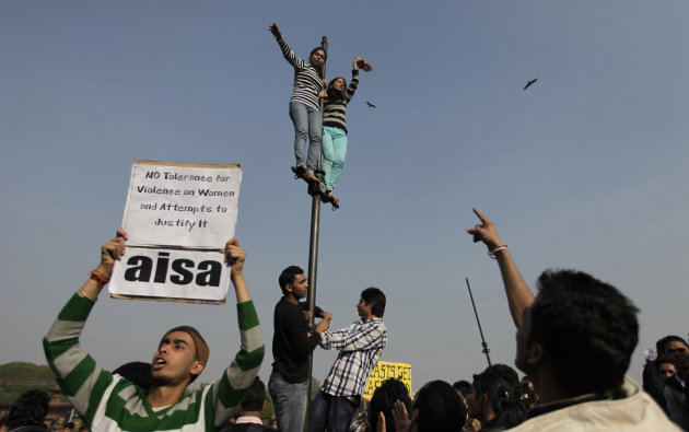 FILE – In this Saturday, Dec. 22, 2012 file photo, Indian women shout slogans from top of a flag post during a protest against the gang rape of a 23-year-old student on a moving bus in New Delhi, Indi