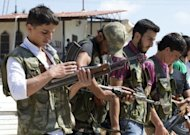 Volunteers for the Amr Ibn Al-Aass brigade load their rifles during training on the outskirts of Azaz, in northern Syria. Syrian rebels seized a crossing on the Turkish border Wednesday even as they quit a swathe of south Damascus that activists said had been reduced to a disaster area by weeks of heavy fighting