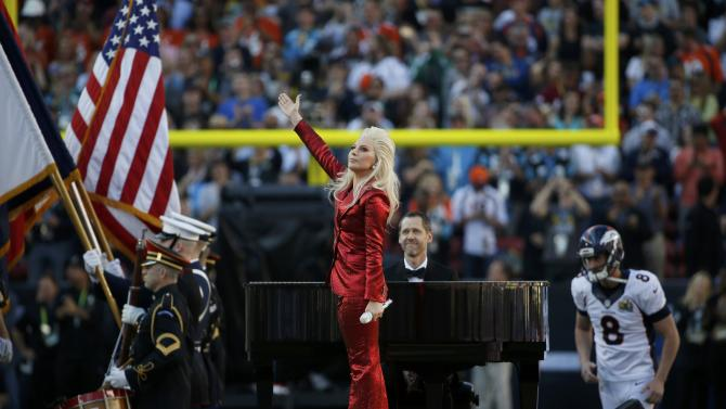 Lady Gaga waves after singing the U.S. National Anthem before the start of the NFL's Super Bowl 50 between the Carolina Panthers and the Denver Broncos in Santa Clara