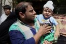 Ali Arar holds his one-year-old wounded son, Aqeel Ali, at the scene of a car bomb attack in the Sadr City neighborhood in Baghdad, Iraq, Thursday, May 16, 2013. A car bomb explosion in a sprawling Shiite neighborhood of Baghdad has killed and wounded dozens of people, officials said. (AP Photo/ Karim Kadim)