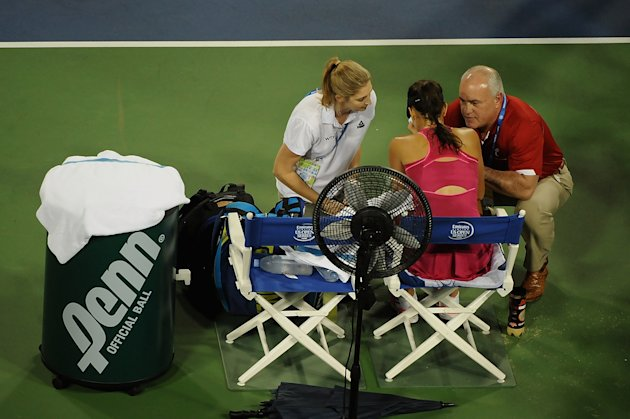 Ana Ivanovic talks with medical staff during a match against Maria Sharapova during their semi-final match Saturday in Cincinnati. (Photo by Jonathan ...