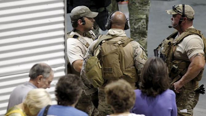 Police officers stand guard at an entrance as attendees are prevented from leaving the Muhammad Art Exhibit and Contest after it was reported that shots were fired outside the venue, in Garland, TX
