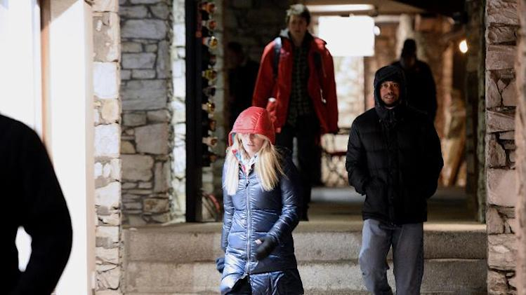 US golfer Tiger Woods (R) and US Alpine skier Lindsey Vonn (C) walk on December 20, 2013, in Val d'Isere, in the French Alps