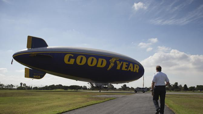 In this July 11, 2015, photo, Matthew St. John, a pilot of Goodyear's Spirit of America blimp, walks toward the blimp at the Goodyear Airship Operations base, in Carson, Calif. The Goodyear Blimp is retiring, but a cigar-shaped craft with its blue-and-gold Goodyear logo emblazoned across the side will still be at sports events, it just won't be technically a blimp. (AP Photo/Jae C. Hong)