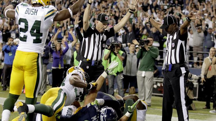 FILE - In this Sept. 24, 2012, file photo, replacement officials signal a touchdown by Seattle Seahawks wide receiver Golden Tate, obscured, on the last play of an NFL football game against the Green Bay Packers in Seattle. If the Packers miss the postseason and the Seahawks make it, Seattle's 14-12 victory in Week 3 on a last-second desperation pass that sparked the end of the lockout of the regular officials will be resurrected endlessly. (AP Photo/Stephen Brashear, File)