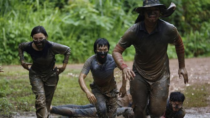 "In this Sept. 14, 2015 photo, film students from Bangkok's Suan Sunandha Rajabhat University are ordered to run through the muddy jungle as part of a grueling endurance test during three days at a military boot camp where they were sent as punishment for a hazing incident in Nakhon Nayok province, Thailand. In military-ruled Thailand there is a new method for teaching discipline known as ""attitude adjustment,"" which until now has been used to silence government critics. But there are signs that the mentality of military rule is creeping into civilian issues - like college discipline. (AP Photo/Sakchai Lalit)"