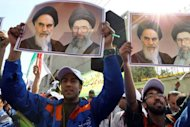 Workers of Iran's Entekhab Industrial Group hold portraits of late founder of Islamic republic, Ayatollah Ruhollah Khomeini (left) and supreme leader, Ali Khamenei as they demonstrate in front of the South Korean embassy in Tehran on October 21. Around 1,000 workers staged a demonstration after an acquisition deal with Daewoo Electronics went sour due to sanctions