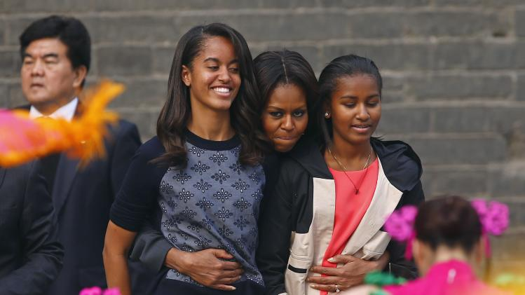 U.S. first lady Michelle Obama hugs her daughters Malia and Sasha as they watch a folk dance by performers during her visit at the City Wall, in Xi'an