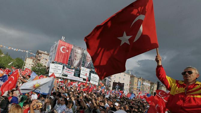 Supporters of Turkish Prime Minister Recep Tayyip Erdogan wave flags as he addresses a party rally outside Ankara, Turkey, Saturday, June 15, 2013. Erdogan said Friday he has asked a small delegation of protesters to convince those occupying a park to withdraw, adding that he is hopeful their protest action would end soon.(AP Photo/Burhan Ozbilici)